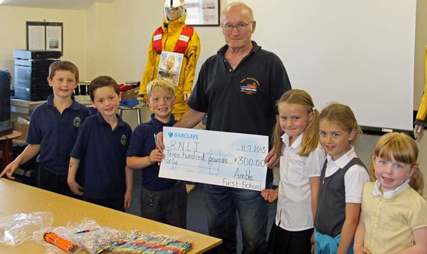 These children all have a relation connected with the RNLI.  Matthew, Kieran, John, Abby, Olivia, Lyla presenting the cheque to Rodney Burge, Amble Lifeboat Operations Manager