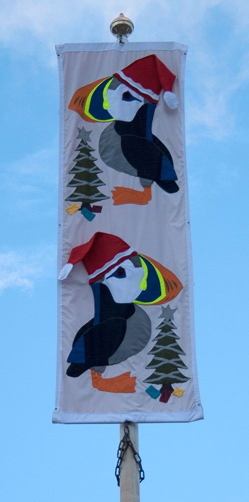 Puffins wearing Santa hats on a banner in Amble Town Square