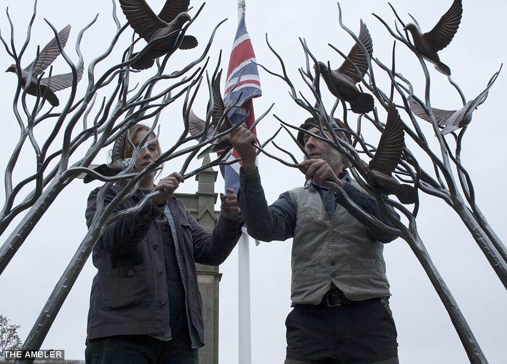 Ashlee and Stephen adjusting peace sculpture