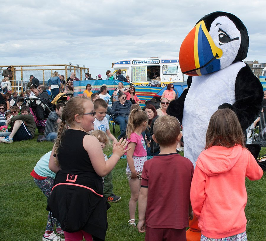 children dancing with Tommy the Puffin
